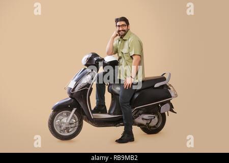 Heureux à la man sitting on scooter et posant avec un casque placé sur sa cuisse et la main posée sur elle. Photo Stock