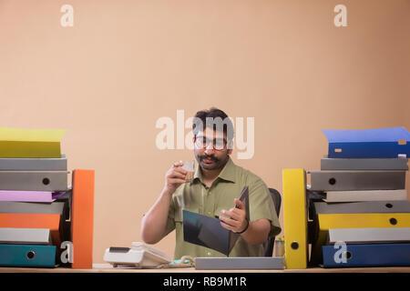 L'étude d'affaires fichiers tout en buvant du thé assis à son bureau en bureau. Photo Stock