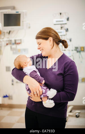 Mère standing in hospital ward holding baby son (6-11 mois) Photo Stock