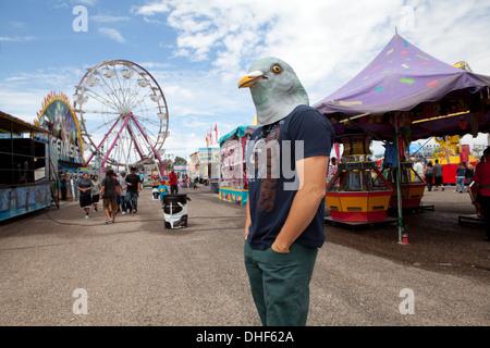 Un homme portant un masque de pigeon se tient à la foire de l'État du Nouveau Mexique avec la grande roue en arrière-plan. Photo Stock
