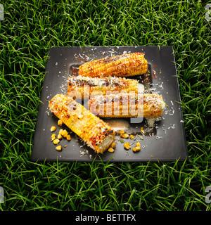 Les épis de maïs au barbecue avec le fromage, le beurre et le piment sur un fond d'herbe. Photo Stock