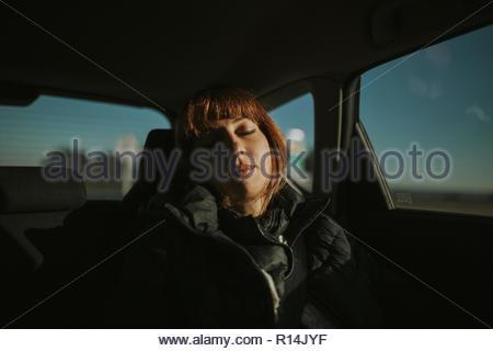 Une femme dort dans une voiture Photo Stock