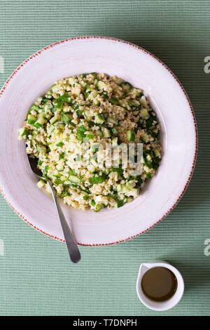 Le taboulé concombre Salade avec un pichet de vinaigrette. Photo Stock