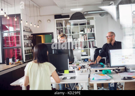 Deux femmes et un homme working in office Photo Stock