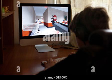 Treize ans boy playing video game Team Fortress sur ordinateur, le jeu en ligne avec des amis. Photo Stock