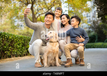 Heureux de prendre une jeune famille avec leur chien selfies Photo Stock