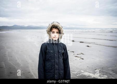Un jeune garçon se tenant sur la plage à Porthmadog. Photo Stock