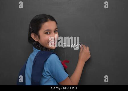 Fille de l'école rurale écrit l'équation d'Einstein sur un tableau noir Photo Stock