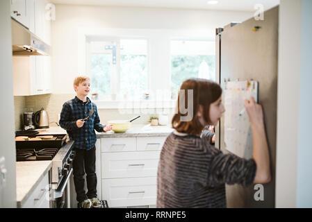 Frère et soeur la cuisson et de l'écriture sur le calendrier dans la cuisine Photo Stock