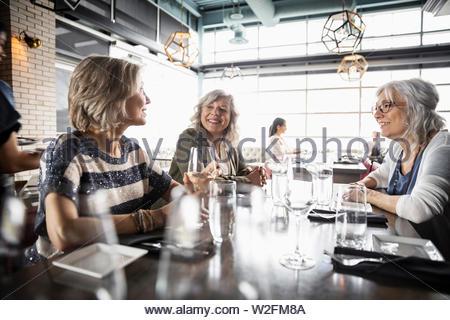 Les femmes âgées amis manger dans restaurant Photo Stock