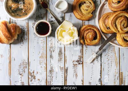 Variété de pâte feuilletée faite maison à la cannelle brioches et croissants servis avec une tasse à café, confiture, beurre blanc déjeuner sur fond de bois en planches. Photo Stock
