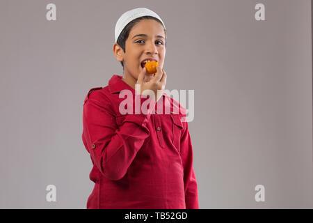Jeune garçon musulman wearing cap de manger des sucreries Photo Stock