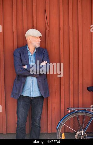 Vieil homme et vélo en avant du mur rouge. Portrait d'une personne âgée avec mode de vie sain. Photo Stock