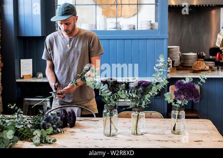Homme portant un chapeau de base-ball debout à une table de coupe, des arrangements de fleurs de chardons dans de grands pots de verre. Photo Stock