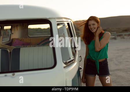 Portrait of beautiful happy young woman standing près de camping-van at beach Photo Stock