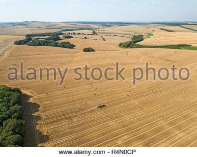 Paysage de l'antenne de la ramasseuse-presse tracteur bottes de paille dans les champs agricoles après la récolte du blé en été Photo Stock