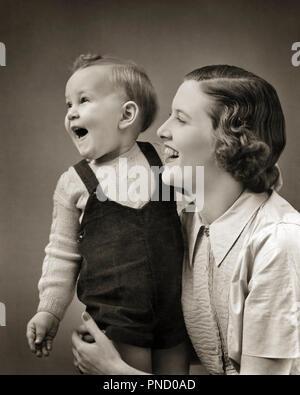 1940 LAUGHING BABY BOY TODDLER DEBOUT APPUYÉE PAR SMILING MOTHER - b4375 HAR001 1 HARS DU VISAGE JUVÉNILE DES JEUNES ADULTES RIRE HEUREUX JOIE solide équilibre de vie LES FEMMES DE SANTÉ ACCUEIL DEMI-LONGUEUR DE LA VIE DES PERSONNES QUI S'occupent d'INSPIRATION MESDAMES EXPRESSIONS MÂLES B&W LE BONHEUR DE LA TÊTE ET DES ÉPAULES DÉCOUVERTE JOYEUSE EXCITATION EN FORCE SOURIRES JOYEUX CONNEXION Bébé garçon élégant ÉMOTION AFFECTION ATTACHEMENT PERSONNEL MINEURS PRIS EN CHARGE LES MAMANS CROISSANCE TOGETHERNESS WOMAN NOIR ET BLANC DE L'ORIGINE ETHNIQUE CAUCASIENNE HAR001 old fashioned Photo Stock