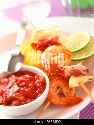 Brochette de gambas cuites avec une sauce tomate et riz safrané Photo Stock