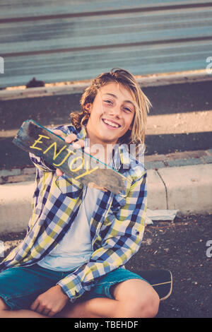 Happy smiling mature jeune adolescent avec hipster occasionnels vêtements montrent travail de motivation profiter written on wood - nice style de personnes et de garçon moderne Photo Stock