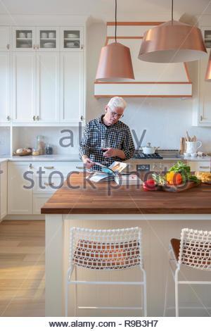 Senior uomo bere il vino rosso e la lettura di un libro di cucina in cucina Immagini Stock