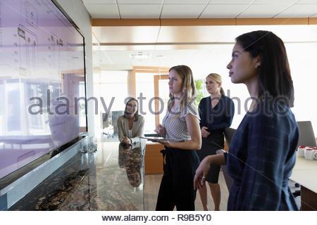 Architetti femmina revisione blueprint digitali sullo schermo del televisore nella sala conferenza incontro Immagini Stock