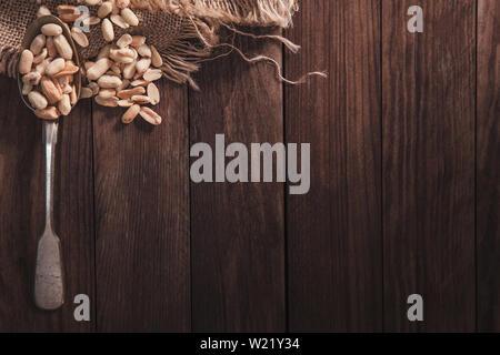 Arachidi tostate su un vecchio cucchiaio e composizione dal vecchio legno e materiale. Vista superiore e spazio vuoto sul lato destro per il testo Immagini Stock