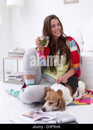 Giovane donna di casa con il cane e tè Immagini Stock