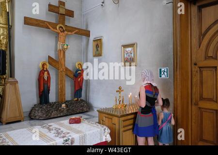 Una donna orante all'interno di San Giorgio e cattedrale di Vladikavkaz la città capitale della Repubblica del Nord Ossetia-Alania nel Nord Caucaso Distretto federale della Russia. Immagini Stock