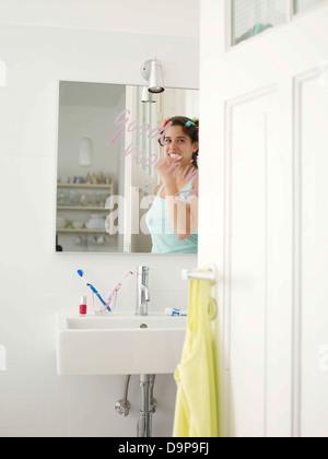 Giovane donna con bigodini in bagno Immagini Stock