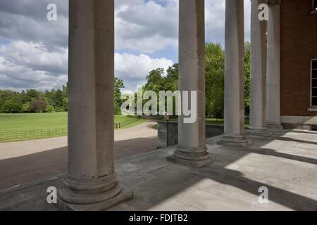 La vista attraverso le colonne del 'trasparente' portico sul fronte orientale della casa, oltre il parco Immagini Stock