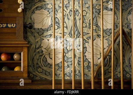 Dettaglio di una parte della sala biliardo con spunti schierate contro la William Morris Pimpernel sfondo, e parte Immagini Stock