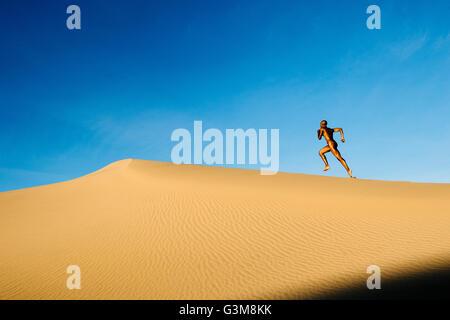 Nudo di donna nel deserto in esecuzione su dune Immagini Stock