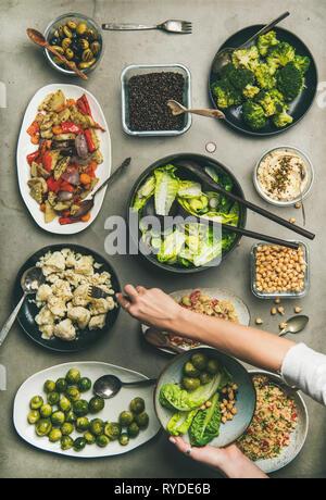 Cena vegana impostazione tabella. Piatti sani in piastre su tavola. Flat-lay di insalate di verdura, legumi, i fagioli, olive, germogli hummus, donna mani taki Immagini Stock
