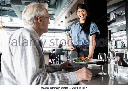 Gentile cameriera che serve il senior uomo nel ristorante Immagini Stock