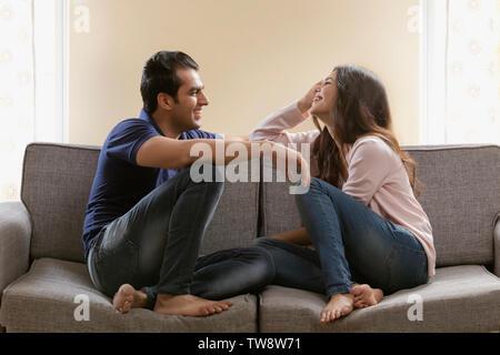 Coppia giovane seduto sul divano di casa Immagini Stock