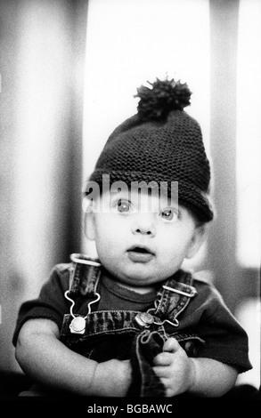 Fotografia di bobble hat bambino wide eyed alert baby funny Immagini Stock