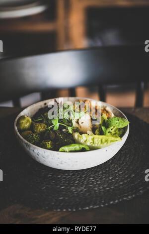 Un sano pranzo o cena impostazione. Vegan superbowl Buddha o ciotola con hummus, verdure, insalata fresca, fagioli, couscous e avocado sul tavolo. Piatti vegetariani Immagini Stock