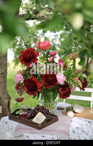 Mazzo di fiori rossi, formaggio, uva e vino rosso Immagini Stock