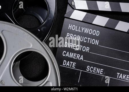 Movie clapper e bobina di pellicola su un sfondo di legno Immagini Stock