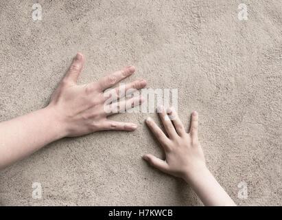 Due mani di connessione. Adulto e bambino mano soddisfare, toccando una parete. Immagine concettuale del collegamento Immagini Stock