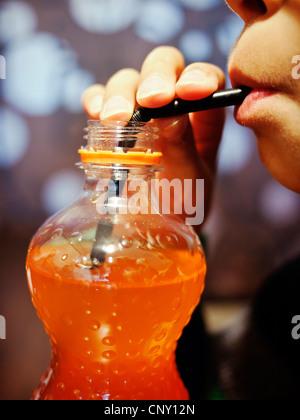 Il ragazzo, paglia, soda arancione. Immagini Stock