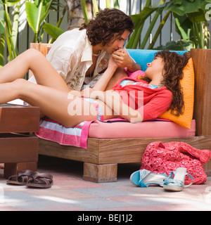 Coppia giovane seduto su un divano e romancing Immagini Stock