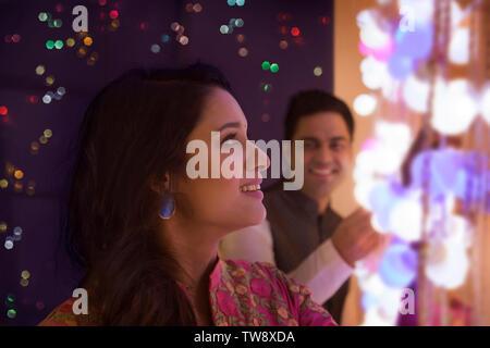 Il marito e la moglie di decorare la casa con le luci sul Immagini Stock