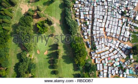 Papwa Sewgolum Campo da Golf, Durban. Incredibili immagini aeree hanno catturato il contrasto e la disuguaglianza in cui ricca incontra poveri di tutto il mondo. La spettacolare vista panoramica foto mostrano il paesaggio come un affluente zona dà modo su uno in cui le persone possono essere affetti da povertà. La scatti sorprendenti mostrano questa crossover di ricchi e poveri tutto il Sud Africa, Kenia, Messico e anche gli Stati Uniti. Le straordinarie fotografie forma di africanDRONE fondatore e fotografo Johnny Miller (37) disparità di progetto Scenes. Johnny Miller / mediadrumimages.com Immagini Stock