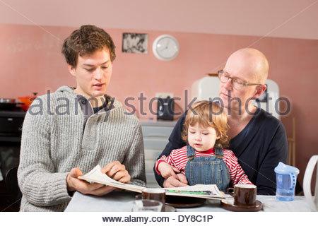 Nonno, il padre e il figlio nella lettura di un libro per bambini Immagini Stock