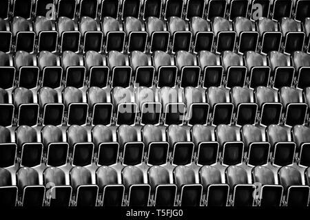 La fotografia astratta di una pila di file di sedili in uno stadio. Immagini Stock