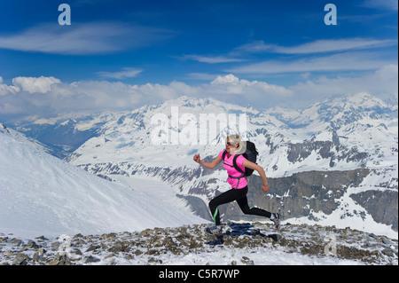 Una donna corre veloce attraverso le montagne nevose. Immagini Stock