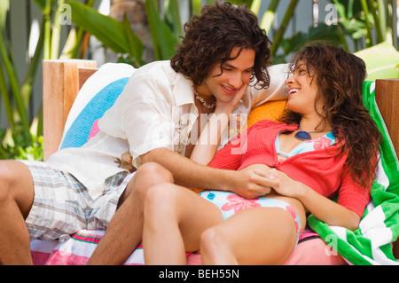 Coppia giovane seduto su un divano e sorridente Immagini Stock