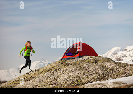 Una donna corre torna alla sua tenda in alta quota sulle montagne. Immagini Stock