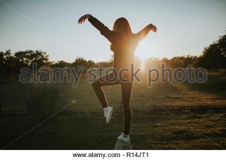 Vista posteriore di una donna con le braccia sollevate su una soleggiata sera Immagini Stock